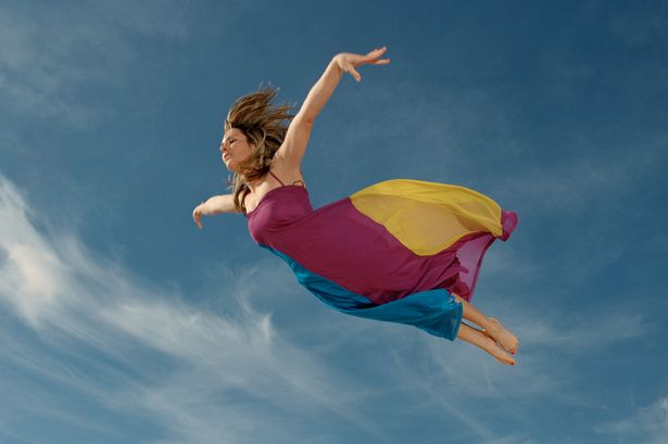 Woman flying through sky, side view